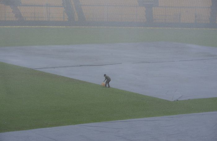 Ground staff cover the pitch at M Chinnaswamy Stadium as rains lash Bengaluru on June 13, 2018
